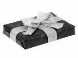 Ręczne pakowanie prezentu - ze srebrną tasiemką i zapakowany w czarny papier.